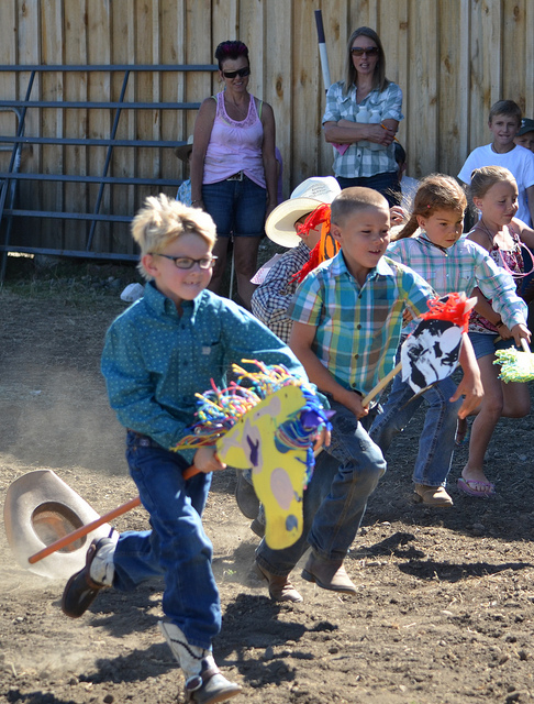 Smiling kids racing stick ponies pretending to be cowboys at the Junior Rodeo