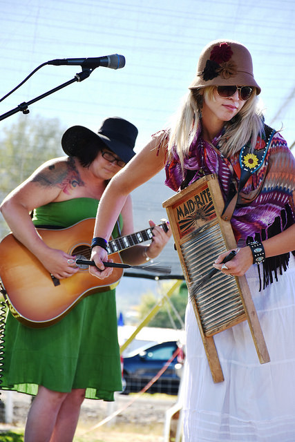 two women musicians performing at Pinefest music festival one playing the washboard and one playing the bass guitar