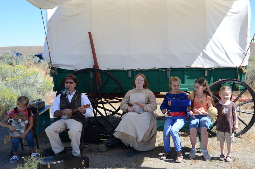 pioneer and children playing vintage musical instruments in front of a covered wagon