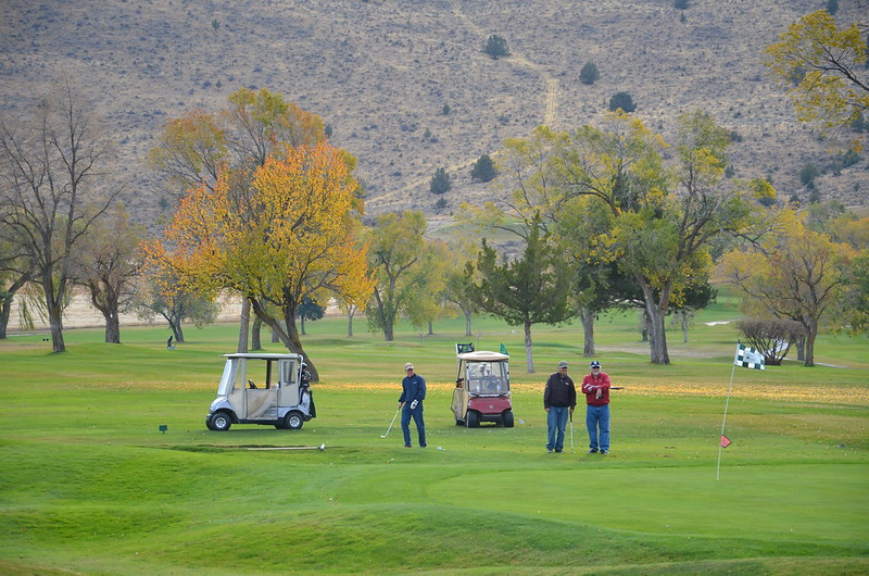 Four golfers finishing a round at the eighteenth hole