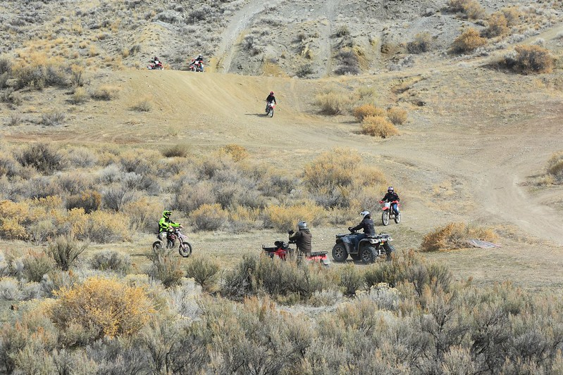 Several dirt bikes and ATVs surrounded by wide open sage brush at the junction of several trails