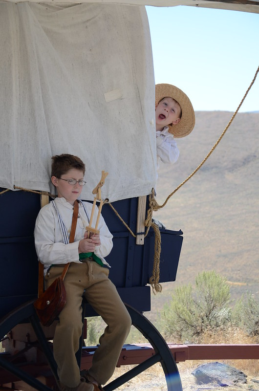 Two pioneer kids playing on a covered wagon
