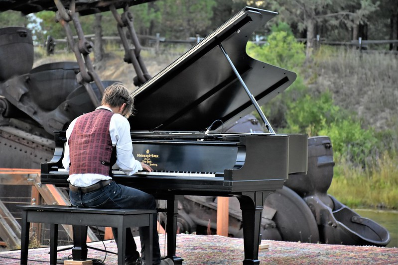 Classical Pianist performing outdoors in front of the Sumpter Valley Gold Dredge