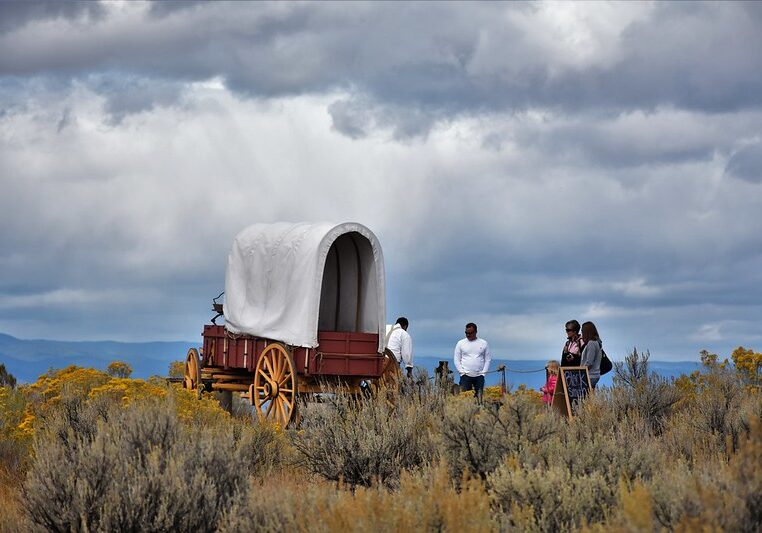 Covered wagon under stormy skies amid the sagebrush on the Oregon trail